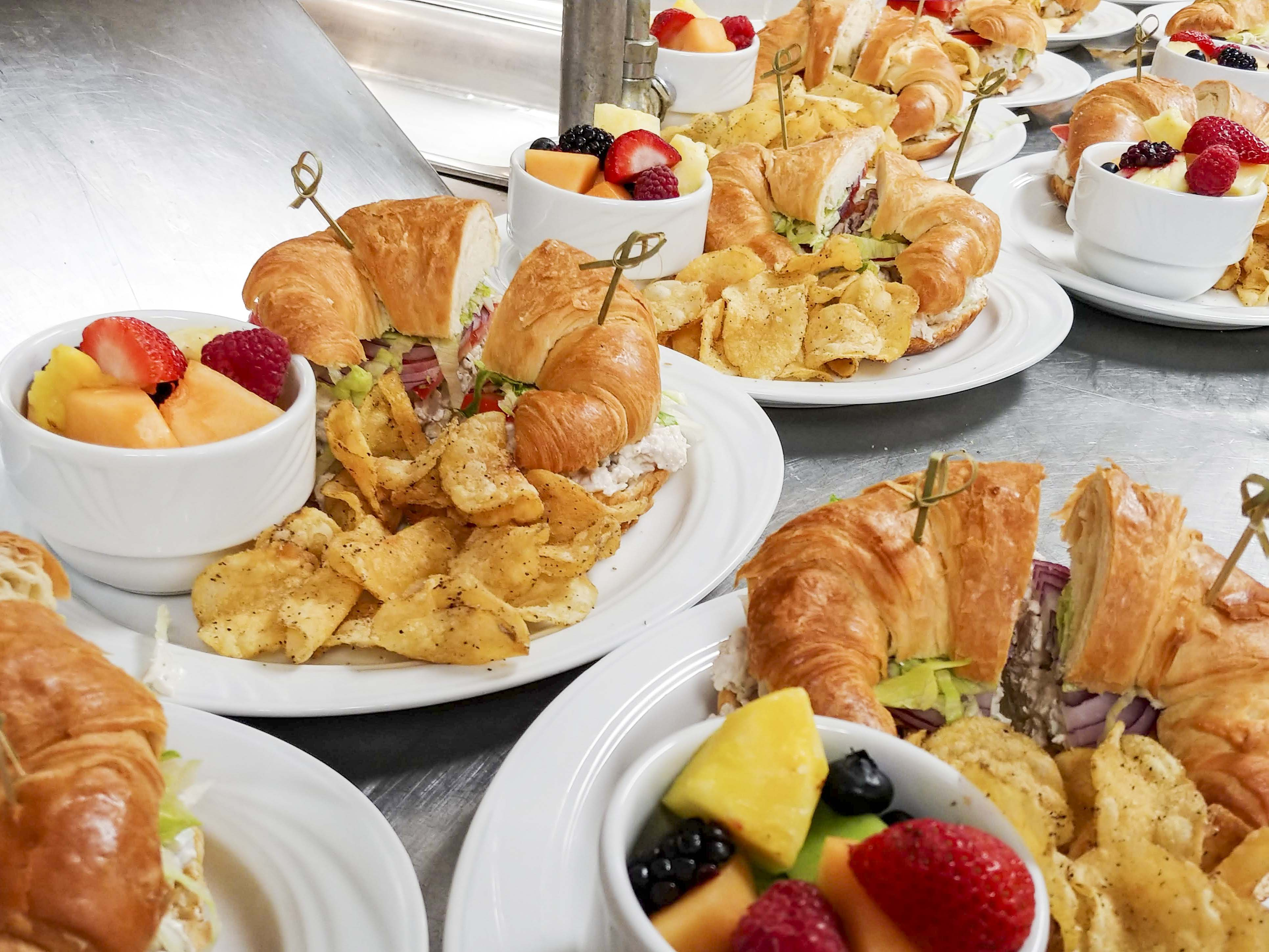 Close up photo of plates of sandwiches, fruit, and chips.